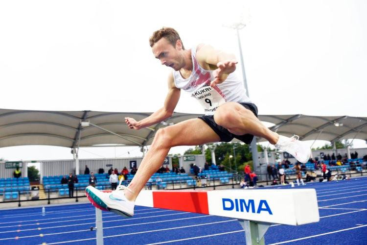 Athlete Will Battershill jumps over a steeplechase barrier on an athletics track at the Manchester International
