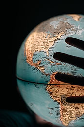 Photo of silhouetted hands on a glowing globe