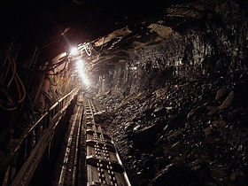 Photo of a tunnel in a coal mine with a light at the end of it