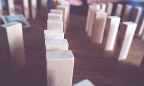 Jenga blocks arranged like dominoes ready to topple