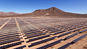 Photo of solar panels in the desert against a mountainour background