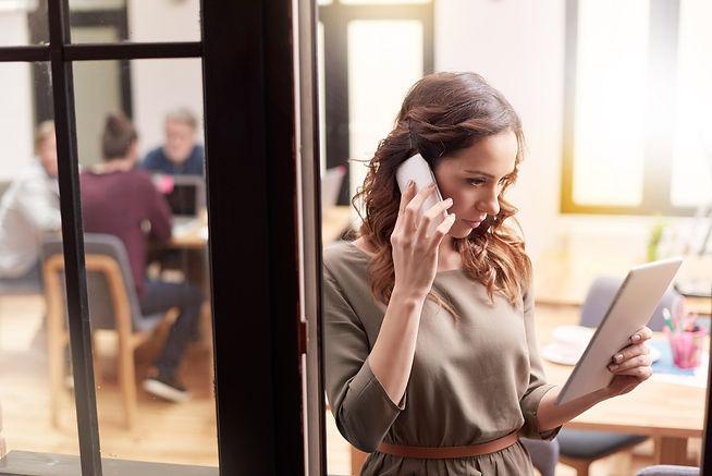 בחורה במשרד מדברת בנייד מסתכלת על טאבלט