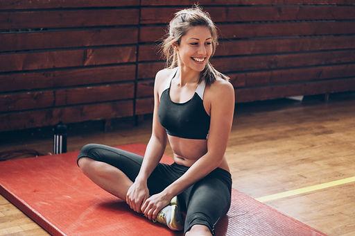 Althetic 여자는 체육관 매트에 스트레칭