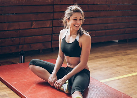 Althetic Mujer que estira en un gimnasio
