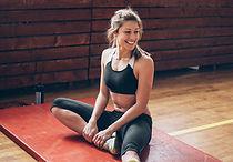 Mujer atlética elongando en un Mat de gi