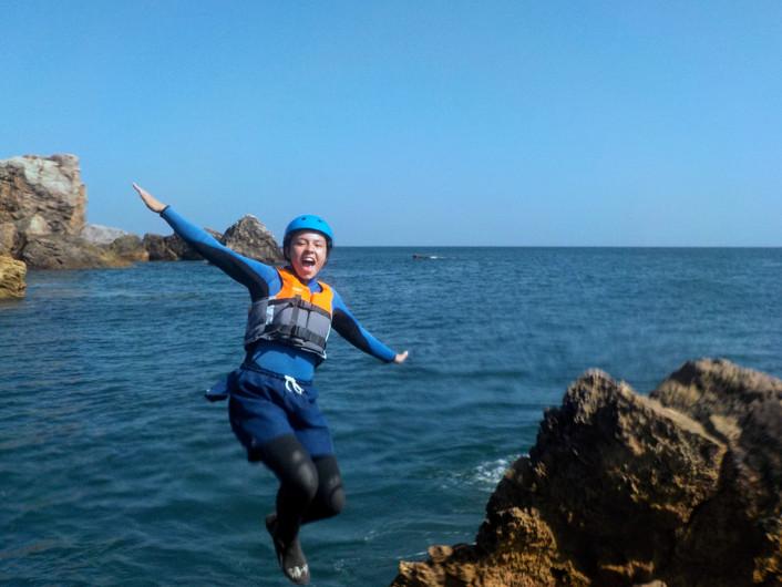 Sorrindo enquanto dá uma pirueta para a água no Algarve