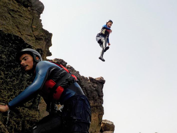 Trepando fora da água e saltando de uma rocha acima