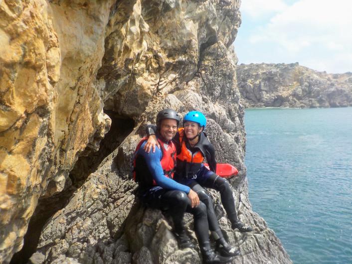 Casal empoleirado numa falésia com vista para o oceano