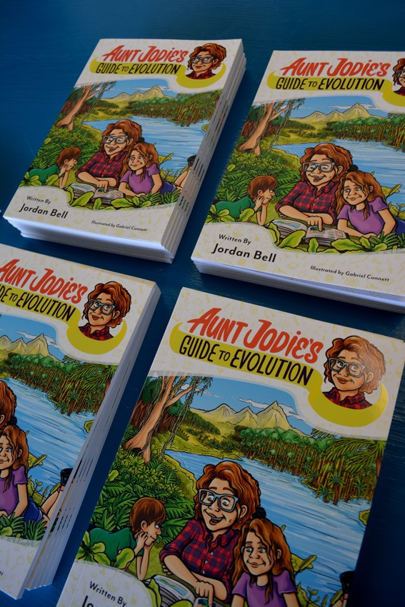 Copies of Aunt Jodie's Guide to Evolution stacked on a blue table