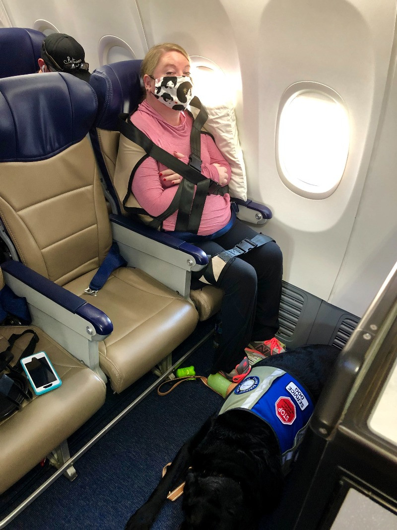 EB Forst wearing a face mask secured onto a seat on an airplane with several straps. Her service dog lies at her feet.