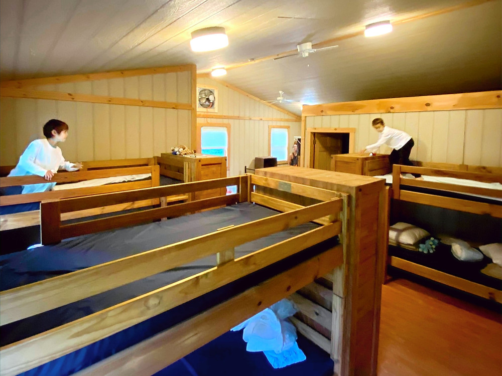 Two young boys explore two top bunks across the room from each other in a wooden cabin.