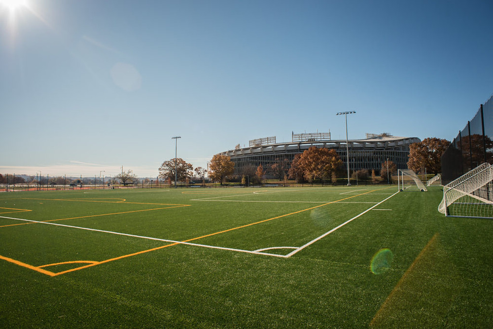 A turf soccer field with RFK stadium in the background.