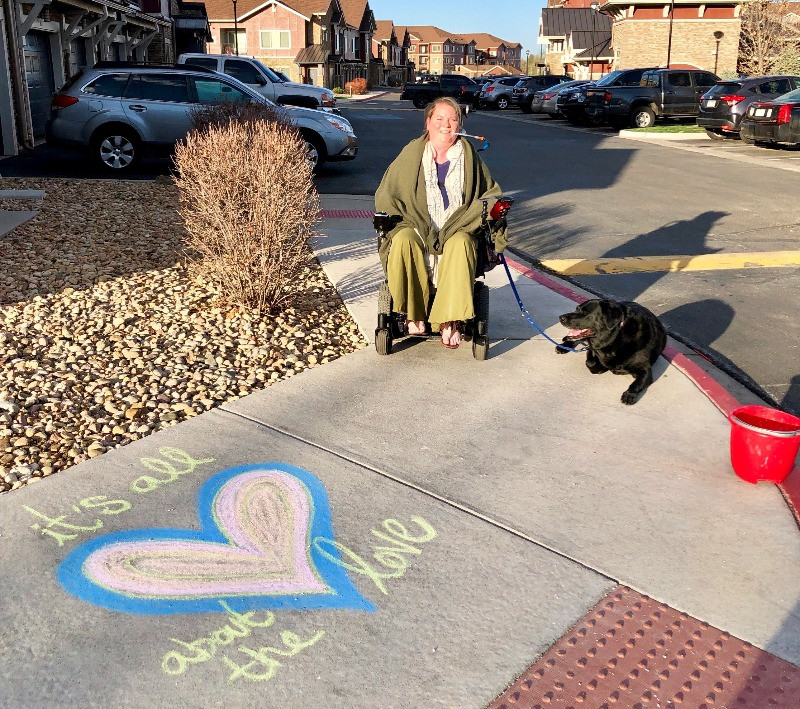 """EB Forst in her power wheelchair on a sidewalk with her dog. The sidewalk art reads, """"It's all about the love"""" with a large heart."""