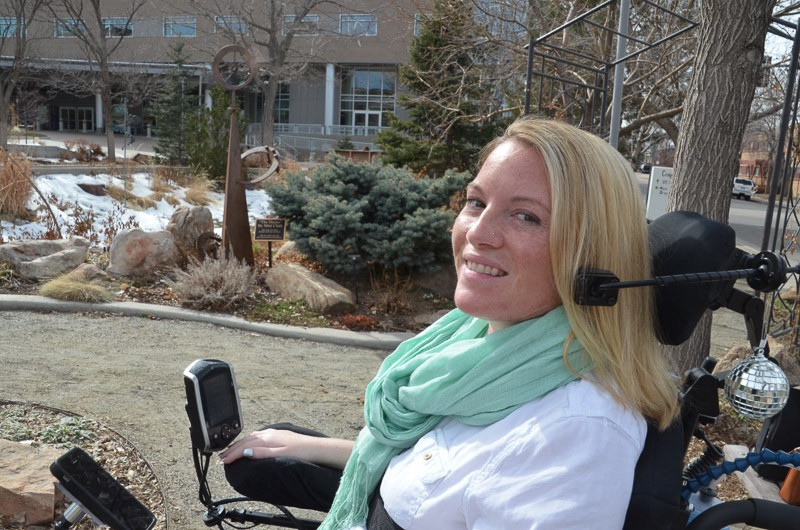 EB Forst from the chest up smiling in her power wheelchair. There are trees, bushes, and snow in the background.
