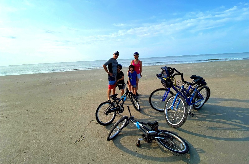 A man, woman, and two young boys stand on the beach wearing bike helmets and summer clothing. The ocean is behind them and their bikes are in front of them.