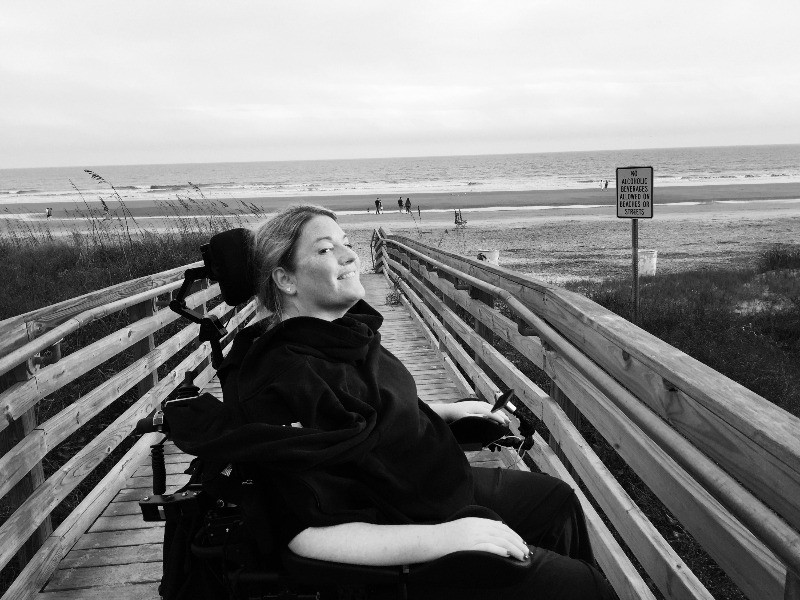 EB Forst n her power wheelchair on a wooden boardwalk that leads to a beach.
