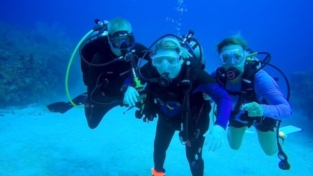 EB Forst underwater wearing scuba gear with two people holding her on either side.