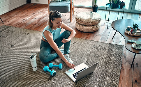 A sporty woman in sportswear is sitting on the floor with dumbbells and a protein shake or