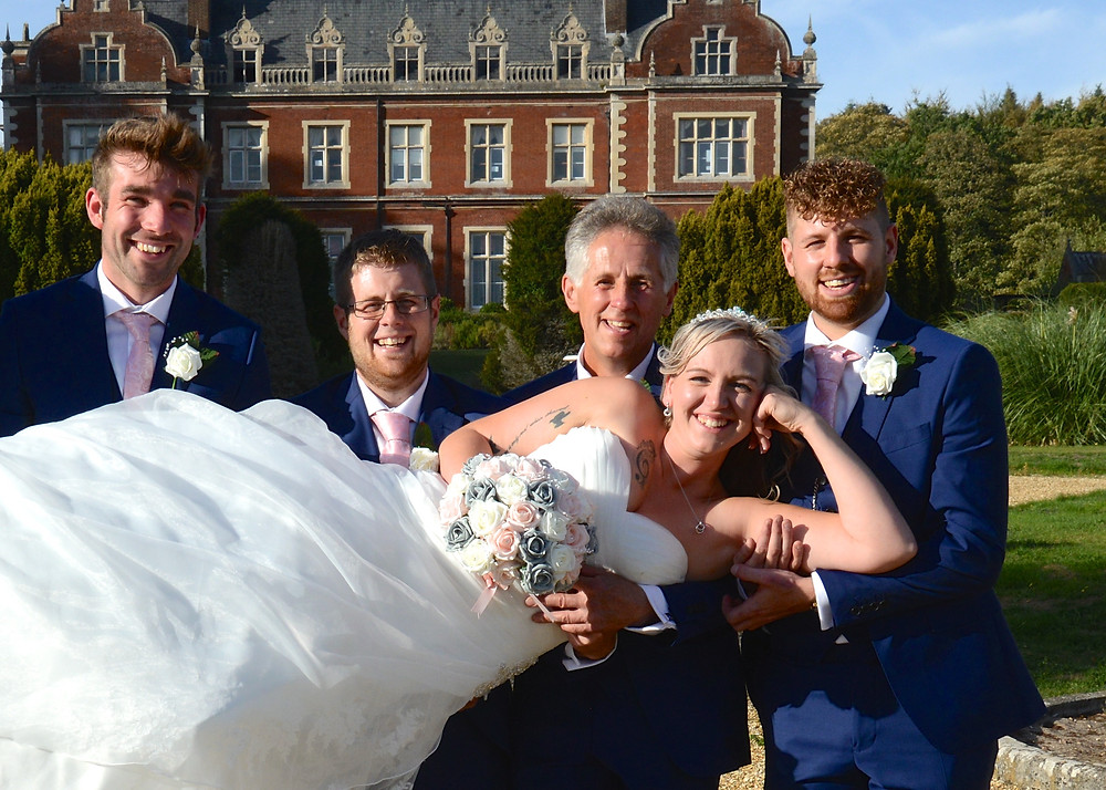 This is Laura being held up by Justin and some of the groomsmen in the rear, sunken Italian garden of Lynford Hall.