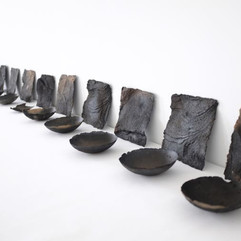 Afton Love   16 Faces and 16 Bowls, 2019   Hand-dug micaceous clay   16 feet (variable) Courtesy of the artist