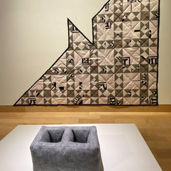 "J. Matthew Thomas  Quilt Construction, 2020  High-density spunbound polyethylene fiber housewrap, geotextile polypropylene/polyester weedblock cloth, Formaldehyde-free R-6.7 unfaced fiberglass wool batts, polyester ribbon, polyester thread  101"" x 101""  Courtesy of the artist"