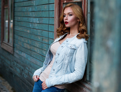Best fahsion photography in Dubai: Lifestyle model with stunning makeup wearing a denim blue jacket leaning against a green building.