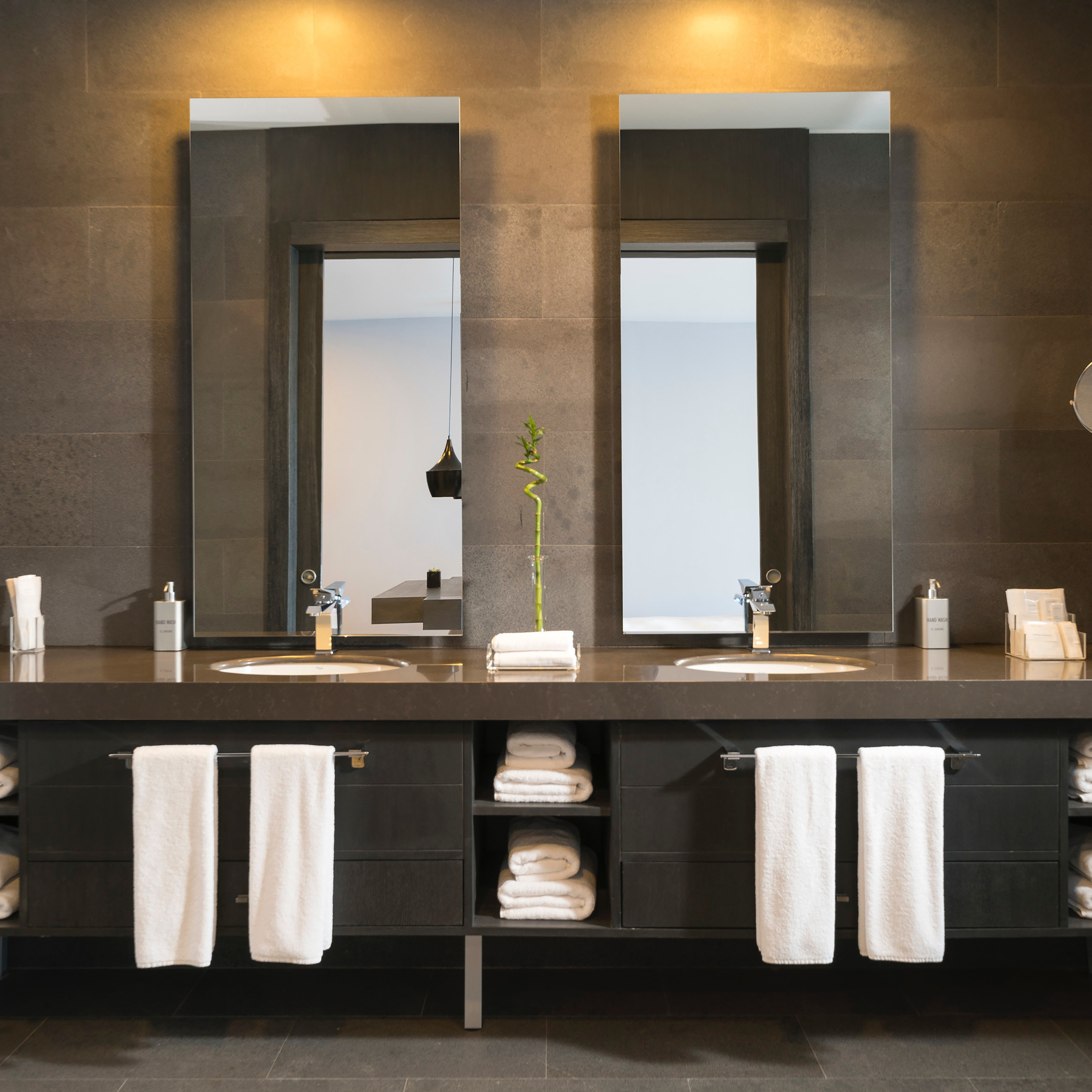 stunning interior photography of a bathroom with towels and mirror and well lit up