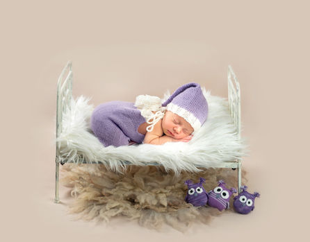 Newborn sleeping on a miniature bed