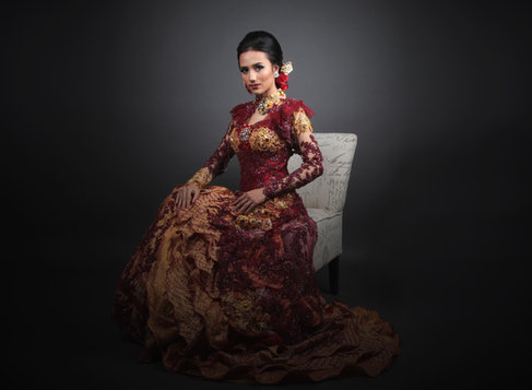 Indian bride wearing a red gown sitting on a white chair. Image captured by bridal fashion photographer in Dubai.
