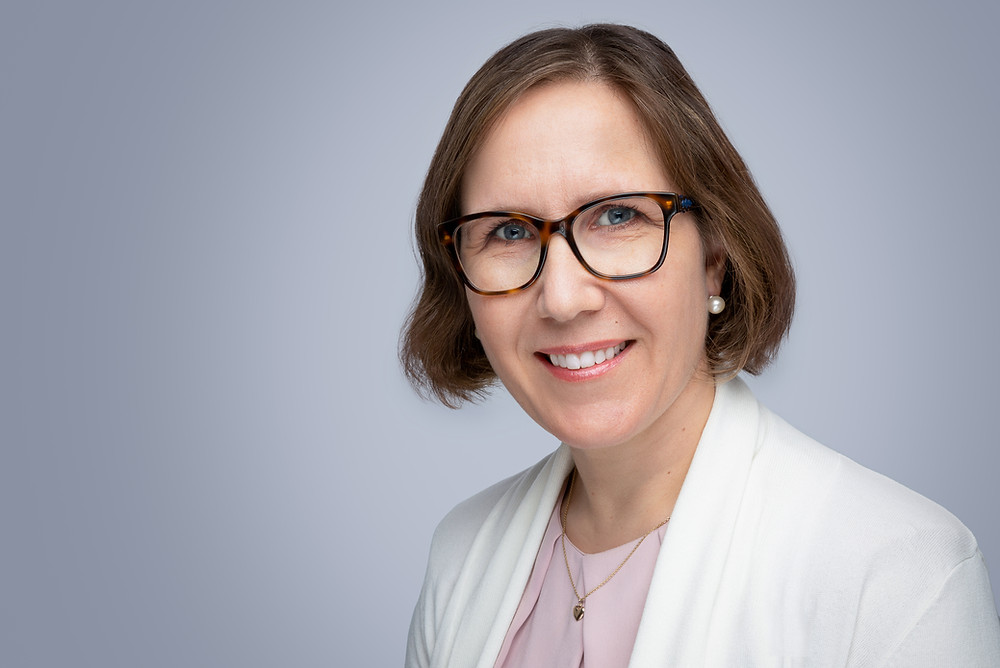 Lady with glasses posing for a professional corporate headshot