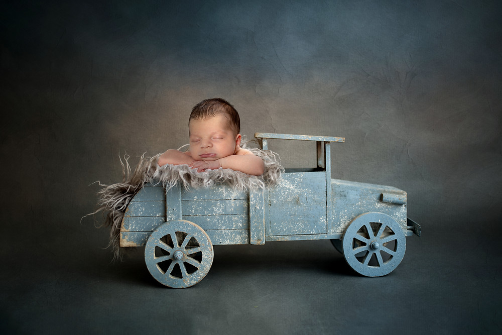 Newborn baby in a blue truck during a photography session in Dubai