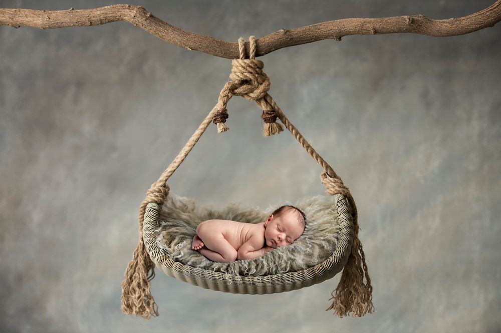 Newborn baby posing on a swing during a photoshoot in Dubai