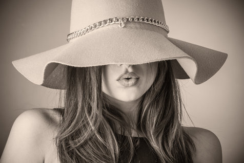 Lifestyle photo shoot: Monotone image of a girl with beautiful makeup wearing a big hat in Dubai.