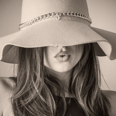 Dubai fashion photography: model with beautiful hair and makeup wearing a hat for a photo shoot.