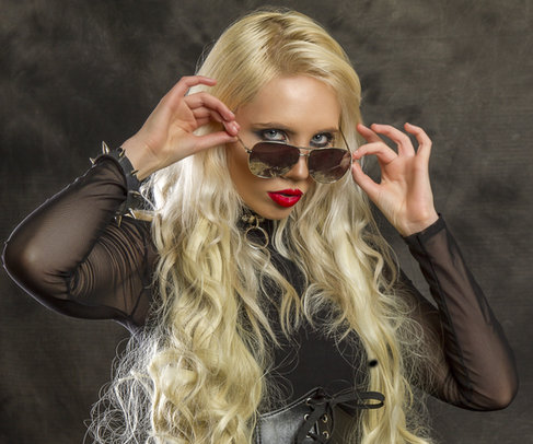 Fashion photo shoot in Dubai: Blonde model with beautiful hair, creative makeup and plump red lips wearing sunglasses and a black top.