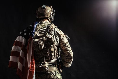 us military with flag.jpeg