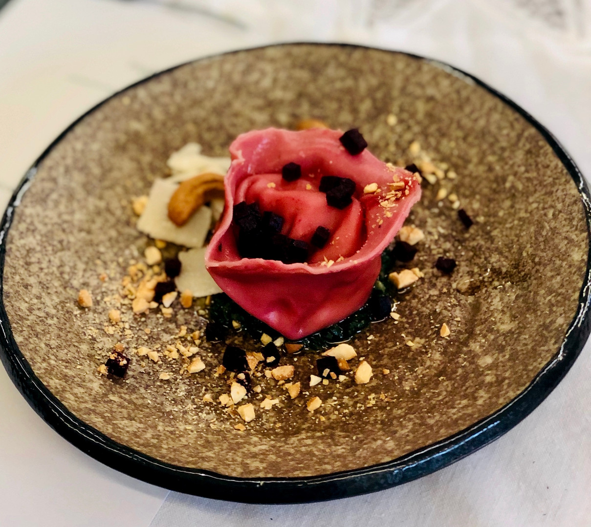 Vegetarian starter for dinner party: beetroot ravioli with cashew nut crème