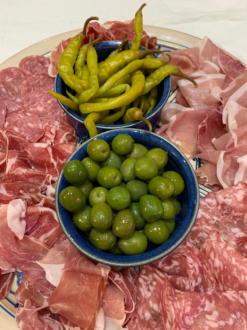 Picnic or starter for a party: cured meats, olives and padron peppers