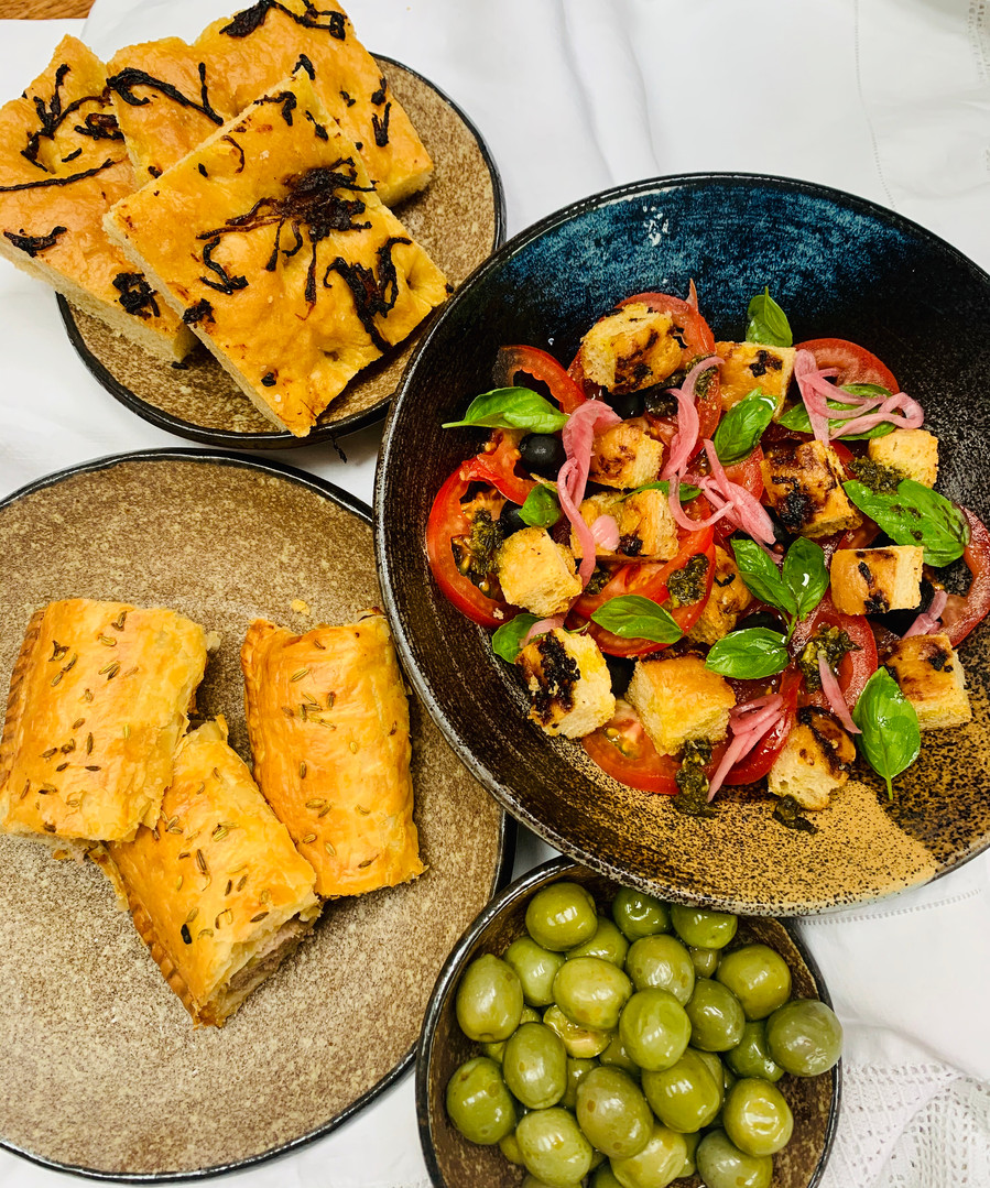 Picnic with panzanella salad, olives, sausauge roll and caramelised red onion focaccia