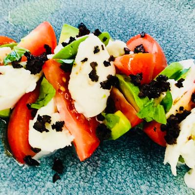 Summer salad for a picnic: mozarella, tomatoes, tricolore, black olive crumb