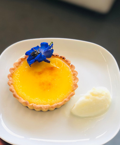 Individual fresh lemon tart with clotted cream ice cream and edible flower