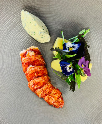 Lobster tail glazed with lobster shell oil, confit potatoes and edible flowers
