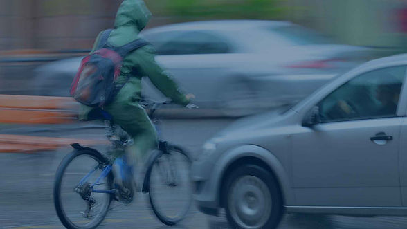 person riding bicycle in the rain in front of a car