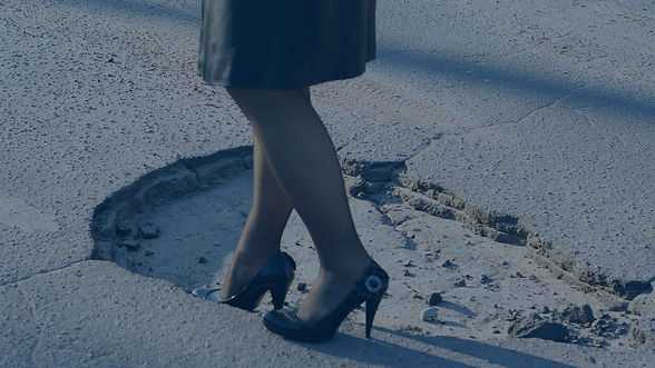 woman in high heels walking on a broken sidewalk