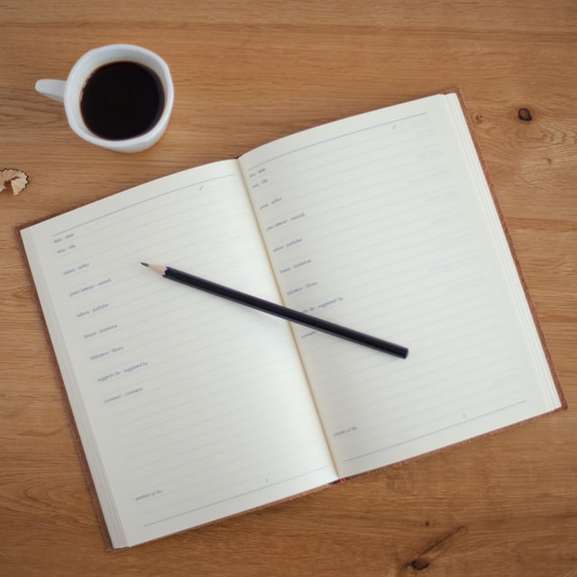 open planner with pencil on desk