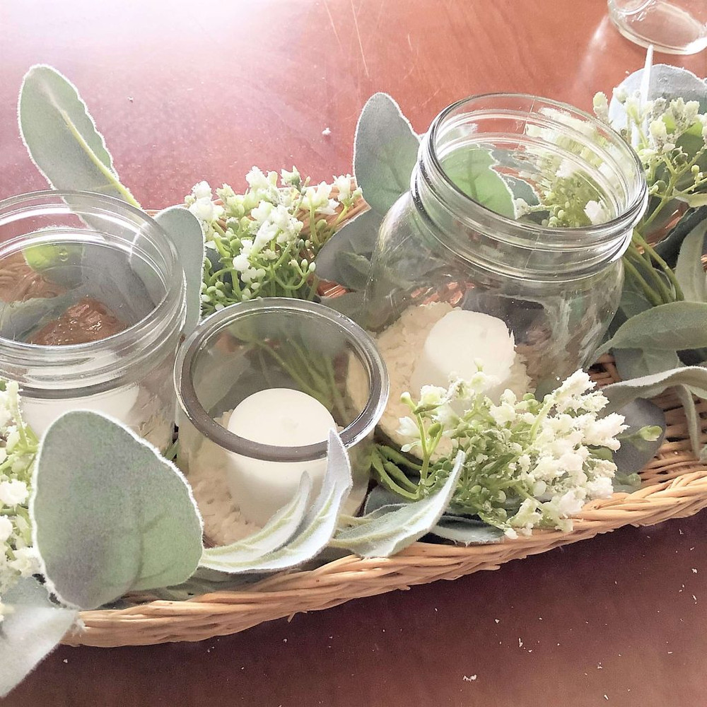basket with jars, candles, and greenery