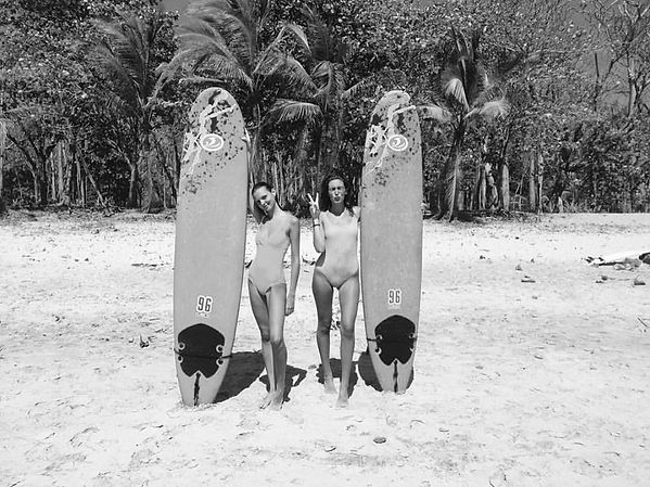 two lovely ladies each holding a surf board