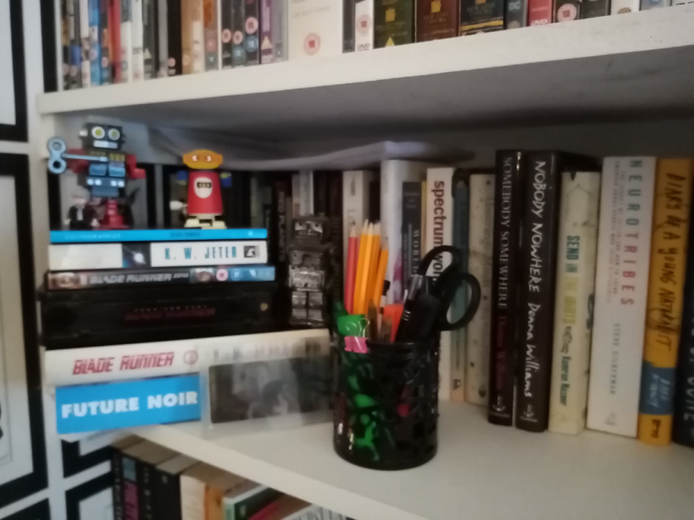 A bookshelf with: a stack of books about Blade Runner with three toy robots on top. There is also a pot of stationary and lots of books about autism in the background