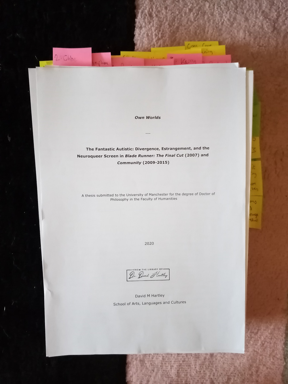 A pile of papers seen from the top: it is a print out of my novel and thesis. There are coloured tags sticking out of the top and the right hand side