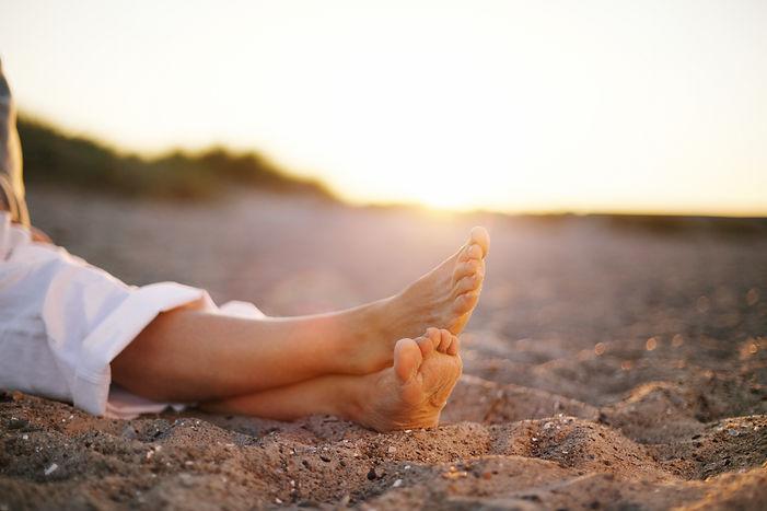 Closeup image of legs of senior woman sitting relaxed on sandy beach..jpg